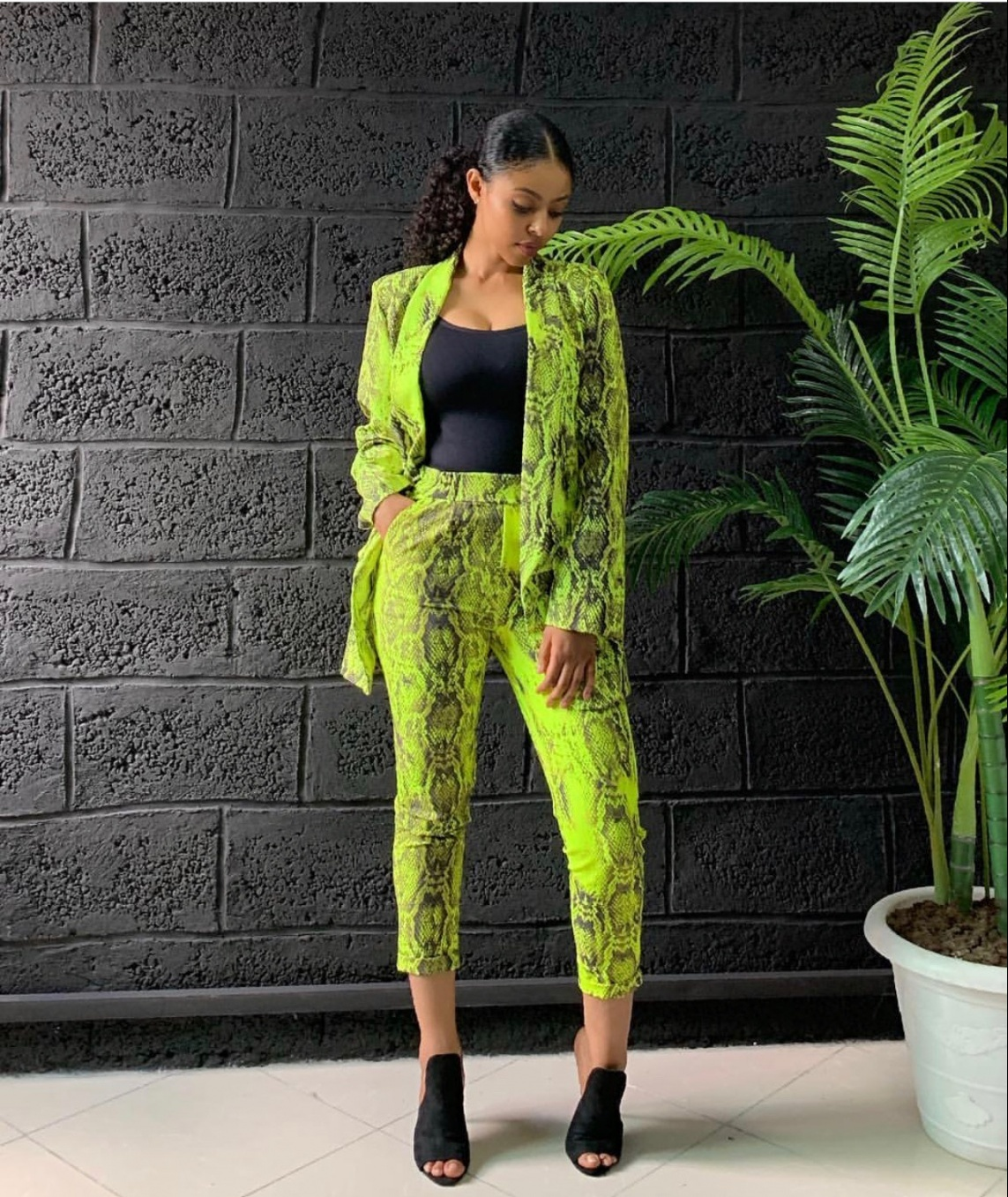 Image of a lady wearing a neon green print suit